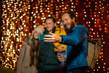 Father taking selfie with family at Christmas market on the night.