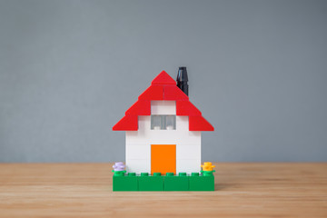 Small and simple house made of toy building bricks, on a wooden surface, gray background. Viewed from the front.