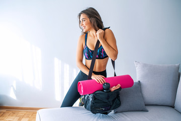 Young woman packing sports stuff for training into bag in living room. Space for text