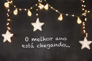 """""""o melhor ano está chegando"""" in portuguese means """"the best year is coming"""" in black background with blurred white stars and yellow light."""