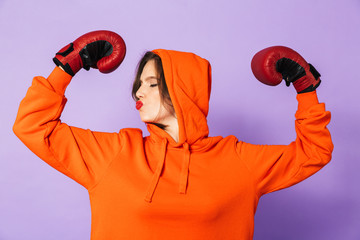 Strong young woman boxer posing isolated over purple background wall wearing boxing gloves.