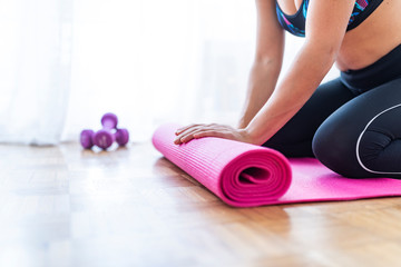 Meditation session, fitness healthy mindful lifestyle concept. Hands of fit woman rolling fitness, pilates, yoga mat before or after working out in yoga studio club or at home on floor. Close up view