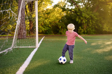 Little boy having fun playing a soccer/football game on summer day. Active outdoors game/sport for children.