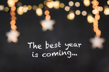text the best year is coming in black background with blurred stars and light