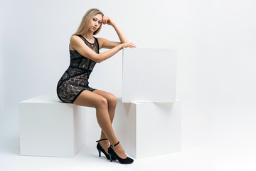 Concept portrait of a beautiful blonde girl smiling on a white background advertises product.