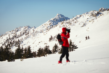 Blurred silhouette of the photographer on a background of snow-covered mountain range.
