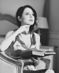 Young redhead woman sitting in chair in bedroom and reading book.