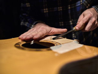 Fastening the neck to the Soundboard of the guitar. Removing the varnish from the Soundboard.