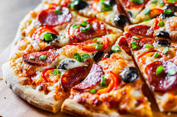Pizza with Mozzarella cheese, pepperoni, tomato, pepper, olive, salami. Italian pizza on wooden table background