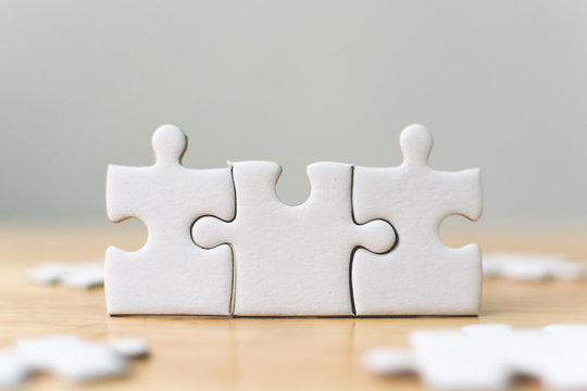 White jigsaw puzzle connecting together. Team business success partnership or teamwork concept