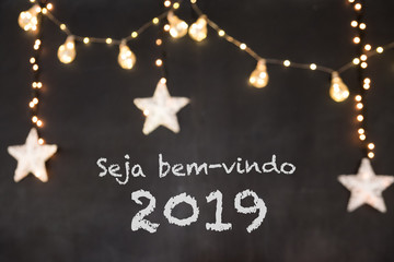 Seja bem-vindo in portuguese means Welcome in a black background with blurred lights and stars.