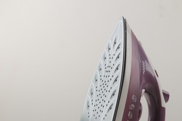 lilac iron on a light background. ironing clothes. household electrical appliances.