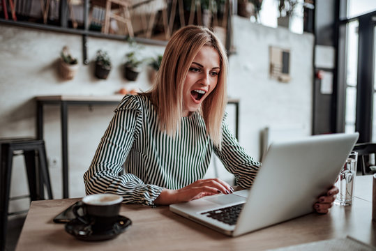 Positive surprised young woman looking at laptop screen.