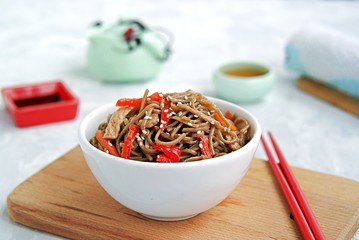 Buckwheat soba noodles with pork, carrots and sweet peppers in a white bowl. Japanese food. The dish is sprinkled with white sesame.