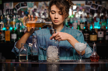 Female bartender pouring to the steel jigger an alcoholic drink
