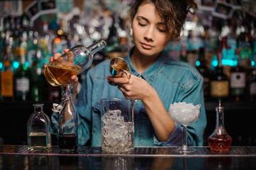 Woman pouring to the measuring glass cup with ice cubes an alcoholic drink from jigger