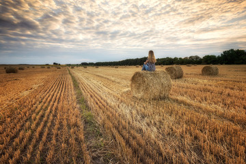 Summer field / Landscape with a woman  in a field full of hay bales before sunset