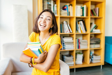 Happy girl student with stack of books in library, education and university concept
