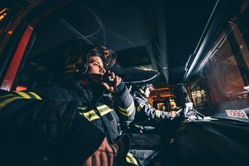 Two Fireman Man posing inside the truck