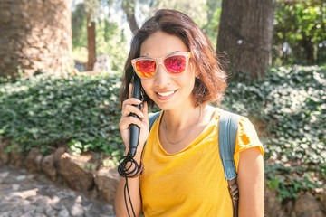 Happy asian woman traveler listen to audioguide