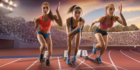Female athletes sprinting. Three women in sport clothes run at the running track in professional stadium Wall mural