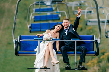 Happy wedding couple riding cableway from mountain in summer. Smiling cheerful bride in white elegant dress lying on grrom shoulder in cable car. Funny groom showing devil horns gesture with hand.