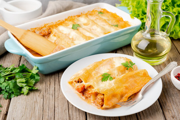 Cannelloni with filling of ground beef, tomatoes, baked with bechamel tomato sauce, side view, old dark wooden background