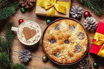 Christmas pie and cup of coffee with heart shape and gift boxes around on wooden table. Hight angle point of view