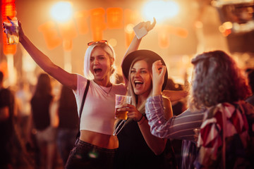Female friends cheering with beer at music festival
