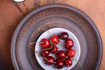 Fresh cherry on wooden plate. fresh ripe cherries. Top view. sweet cherries.