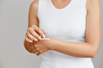 Closeup shot of woman hands holding cream and applying moisturizing hand cream. Beautiful female hands with cream. Hand Skin Care. A woman uses body lotion on your arms. Beauty And Body Care Concept