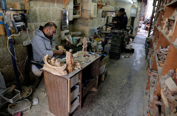 Palestinian workers carve figurines for sale during Christmas season, at a workshop in Bethlehem