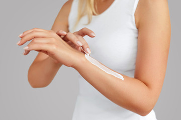 Closeup of female hands applying hand cream.Hand Skin Care.  Women use body lotion on your arms.  Beauty And Body Care Concept