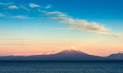 View of Osorno volcano, Puntigudo volcano and Llanquihue Lake in the Chilean Lake district at sunset.