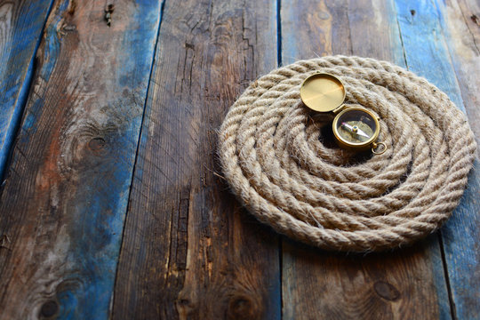 Pirate and nautical background with an old weathered deck, rope and compass. With a place for copy space.