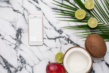 Mobile phone and tropical fruits on marble background