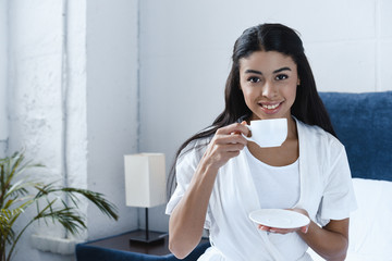 smiling beautiful mixed race girl in white robe drinking coffee and looking at camera in morning in bedroom