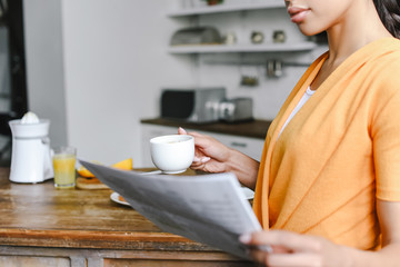 cropped image of mixed race girl in orange shirt holding cup of coffee and reading newspaper in kitchen
