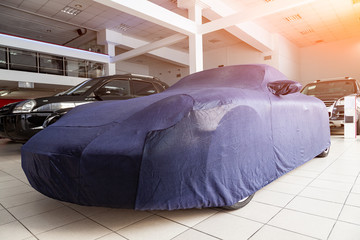 An expensive car is shown in the avtosolon stand among other cars covered with a cover made to order from a special blue fabric, ideal for all elements of the body.