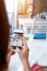 Woman taking photo of white wine on her smartphone in restaurant.