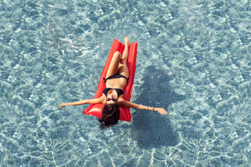 Woman sunbathing on a floating in a pool