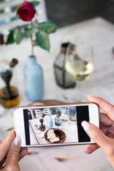 Woman taking photo of bread and wine on her smartphone in restaurant.