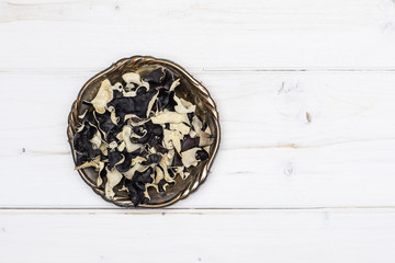 Lot of slices of dry black mushroom jew ear variety in old iron bowl flatlay on white wood