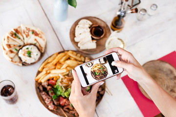 Woman taking photo of mix grill dish using smartphone in restaurant. Bali island.