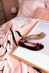 Composition of colorful shoes setting on gold frame with crease pink blanket underneath / cozy interior concept / fashion photoshoot with creative background