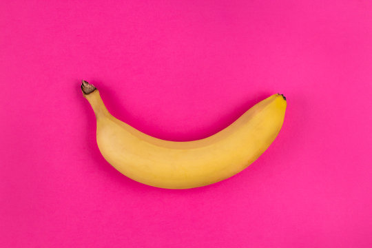 Banana on the pink background. Minimalistic fashion design, bright trendy colors. Copy space, top view, flat lay