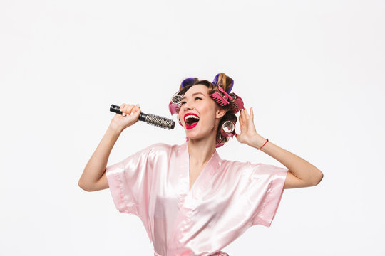 Cheerful housewife with curlers in hair wearing robe