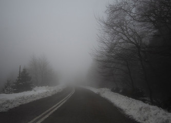 Mountain road, fog, clouds and snow in the forest in the mountains Dirfis on the island of Evia, Greece