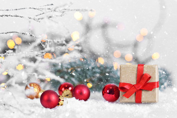 Christmas present with red ribbon on snowy background
