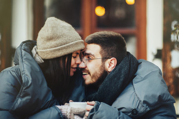 Young romantic couple is having fun outdoors in winter before Ch
